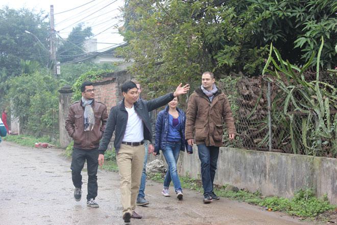 Anh Nguyễn Bá Toàn dẫn đoàn khách phương Tây đến thăm cơ sở kho cá tại làng Nhân Hậu