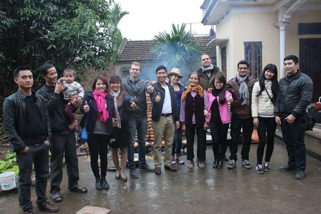 Đoàn khách Tây chụp ảnh lưu niệm cùng những người dân kho cá trong làng